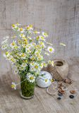 A bouquet of chamomiles in a glass vase on the background of burlap stock photography