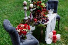 Bouquet cher et à la mode de mariage des roses dans le marsala et couleurs rouges se tenant sur la chaise Détails et décor nuptia Photographie stock