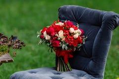 Bouquet cher et à la mode de mariage des roses dans le marsala et couleurs rouges se tenant sur la chaise Détails et décor nuptia Image libre de droits