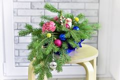 Bouquet of Christmas tree with Christmas decorations and live carnations and roses. On light background stock photos