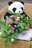Bouquet of Christmas tree with Christmas decorations and lovely flowers. On a wicker chair. Toy bear in the background royalty free stock photos