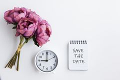 Bouquet, Clock and Note pad with text written - Save the Date. Flat lay of purple flower, clock and note pad with text written ` Save the date` . Conceptual stock photos