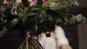 The bouquet is collected from various types of flowers. The florist decorates the stems with a decorative ribbon. Florist girl in the background stock video