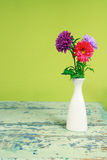 Bouquet of colorful chrysanthemums in a white vase on a vintage Stock Images