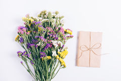 Bouquet of colorful flowers and the book in wrapping paper lying. On a white background, top view Stock Photography
