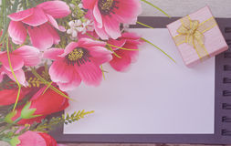 Bouquet of colorful flowers and gift box on open book Royalty Free Stock Photo