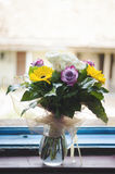 Bouquet of colorful flowers at the window Royalty Free Stock Images