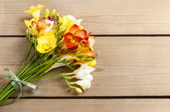 Bouquet of colorful freesia flowers on brown wood Stock Photos