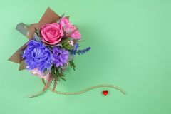 A bouquet of colorful paper flowers and a small red heart on a green background as a backdrop for a postcard, invitation letter an stock photos