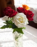 Roses on   white table. Bouquet of colorful roses on  white table stock photos