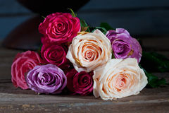 Bouquet of colorful roses on wood Stock Image