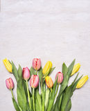 Bouquet of colorful spring tulips on wooden rustic background top view close border ,place for text Royalty Free Stock Photo