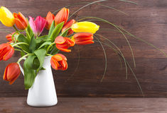 Tulips in a jar. Bouquet of colorful tulips on dark wooden background Royalty Free Stock Photography