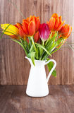 Tulips in a jar. Bouquet of colorful tulips on dark wooden background Stock Image