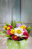 Bouquet of colorful wild flowers in green dotted can Royalty Free Stock Image