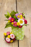 Bouquet of colorful wild flowers in green dotted can. Festive and party decoration Stock Photo