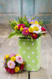 Bouquet of colorful wild flowers in green dotted can Royalty Free Stock Images