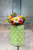 Bouquet of colorful wild flowers in green dotted can Stock Photos