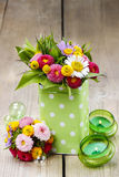 Bouquet of colorful wild flowers in green dotted can Stock Images