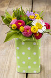 Bouquet of colorful wild flowers in green dotted can. Summer decoration Royalty Free Stock Images