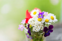 Bouquet of colourful garden flowers in a glass on old tree trunk Royalty Free Stock Photo