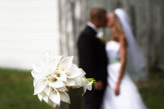 Bouquet with couple kissing. Bouquet in foreground with newlywed couple kissing in background Stock Images