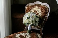Bouquet of cream roses and white orchid on a brown chair Stock Photo
