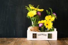 Bouquet d'été des fleurs sur la table en bois et le fond en bois de tableau noir Copiez l'espace Image libre de droits