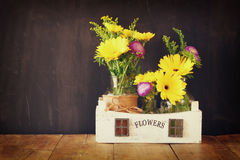 Bouquet d'été des fleurs sur la table en bois et le fond en bois de tableau noir Copiez l'espace Images libres de droits