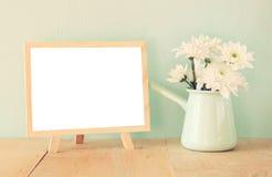 Bouquet d'été des fleurs sur la table et le tableau noir en bois avec la pièce pour le texte avec le fond en bon état image filtr Photos libres de droits