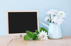 Bouquet d'été des fleurs sur la table et le tableau noir en bois avec la pièce pour le texte avec le fond en bon état image filtr Images stock