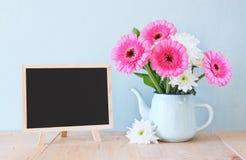 Bouquet d'été des fleurs sur la table et le tableau noir en bois avec la pièce pour le texte avec le fond en bon état image filtr Photos stock