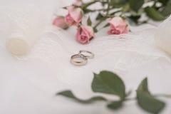 Bouquet d'anneaux et de roses de mariage sur le fond blanc images libres de droits