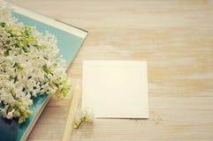 Bouquet d'un lilas blanc sur le livre ouvert et la carte vide blanche pour une inscription Photo libre de droits