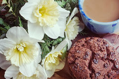 Bouquet of daffodils, cup of coffee and chocolate muffin. Bouquet of daffodils, cup of coffee with milk and chocolate muffin Stock Image