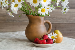 Bouquet of daisies in a clay jug and strawberries with pears Stock Image