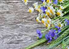 A bouquet of daisies and cornflowers on wooden table Stock Photography