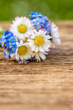 Bouquet with daisies and forget-me-not on a wooden background Stock Photography