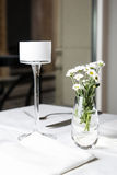 Bouquet of daisies standing in glass vase on white table. Shalow focus stock images