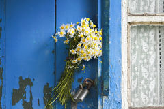 Bouquet of daisies stuck in the handle of the closed door of the old wooden house. A bouquet of daisies stuck in the handle of the closed door of the old wooden Stock Images