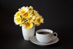 Bouquet of daisies in a vase and a cup of hot coffee / tea on a black background. Horizontal. Space for text stock photos