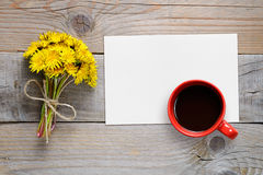 Bouquet of dandelions, blank paper and coffee cup Royalty Free Stock Photos