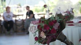 Bouquet dans la trompette de phonographe sur un fond brouillé du hall de banquet banque de vidéos
