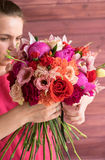 Bouquet dans les mains de la fille en rouge Photos stock