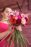 Bouquet dans les mains de la fille en rouge Photographie stock