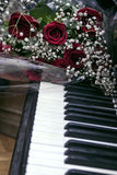 Bouquet of dark red roses on piano Royalty Free Stock Photos
