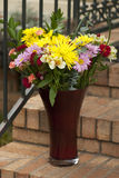 A Bouquet A Day Floral Arrangement. This is a bouquet of mixed flowers in a red glass vase sitting on the brick steps with a black wrought iron backdrop royalty free stock photo
