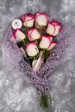 Bouquet de belles roses avec des cosmétiques sur le béton gris Photos stock