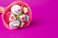 Bouquet de confiture d'oranges et de bonbons dans l'emballage rose sur un fond rose image libre de droits
