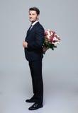 Bouquet de dissimulation d'homme d'affaires des fleurs derrière le sien de retour images libres de droits